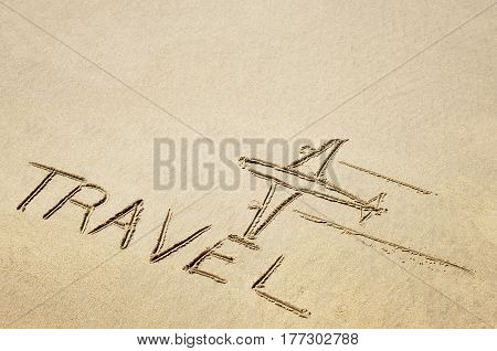 Drawing of an airplane and word travel in the sand on the beach.