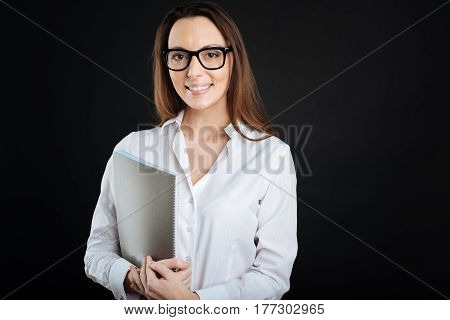 Time for work. Positive delighted female wearing glasses keeping smile on her face while standing isolated on black background