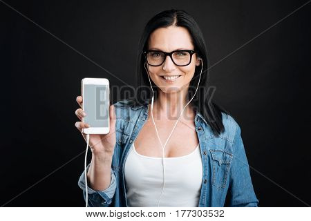 Feeling pleasure. Attractive beautiful young woman showing on the gadget, smiling and feeling pleasant.