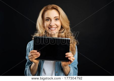 Buy it. Positive delighted female wearing casual clothes looking straight on camera, standing over black background