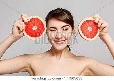 emotions health people food and beauty concept -Beauty portrait of a happy woman holding a grapefruit emotional portrait. The girl winks her eyes