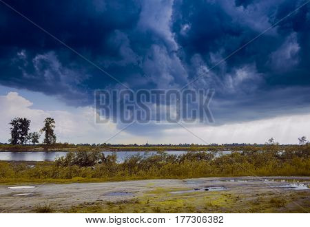 Dramatic sky in the countryside, against a background of a meadow and a river