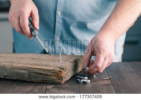 Man's Hand Using Screw Driver Assembling Wooden Plank