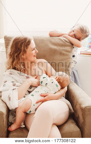 Group portrait of white Caucasian family of three mother breastfeeding newborn baby older sibling sister girl standing watching lifestyle candid real life emotions
