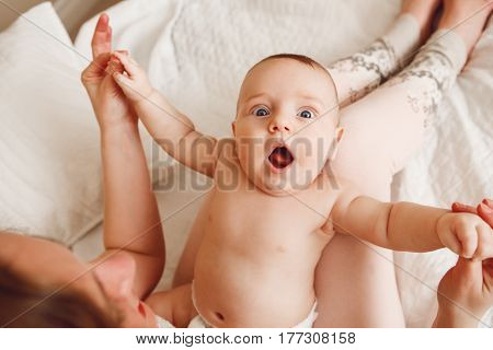 Closeup portrait of cute adorable white Caucasian newborn baby lying on mother lap doing physical exercises together funny surprised face expression early development concept