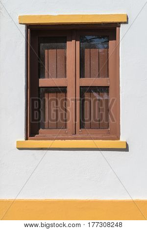 Beautiful traditional brown window on white wall.