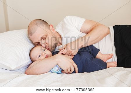 Portrait of middle age Caucasian father in white t-shirt lying in bed with newborn baby son holding his hands fingers kissing in cheek parenting childhood bonding concept lifestyle