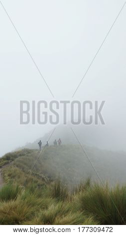 Group of people looking backwards walking towards the summit of the Rucu Pichincha volcano on a cloudy day, near the city of Quito. With copy space