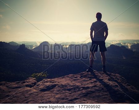 Young Hiker In Black Pants And Shirt On Edge, Look To Valley
