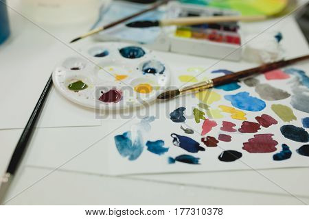 A palette of watercolors and brushes lie on the artist's desk