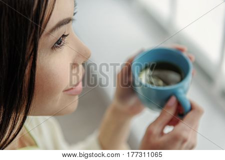 Focus on face of smiling asian woman drinking delicious beverage. Pleased concept