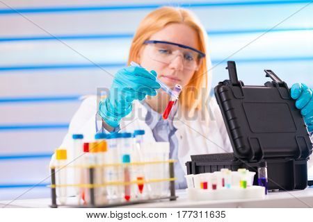 Laboratory assistant in a laboratory with a toxic biological sample in test tube
