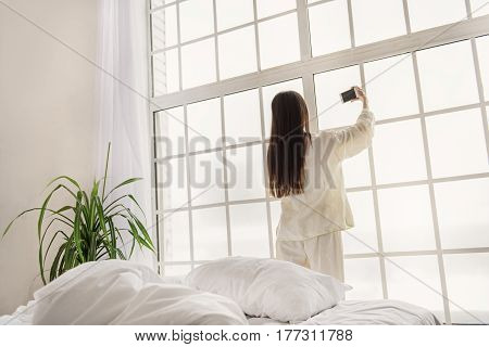 Serene young female taking photo by mobile while standing near wide window