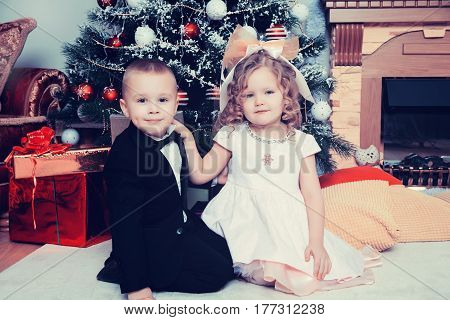Well-dressed boy and girl sitting near a Christmas tree surrounded by gifts.Creative toning of a photograph.