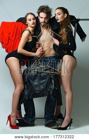 Two pretty sexy women in black bodysuits and red high heels hugging bearded man with muscular torso with clothing on hangers at clothes rack wardrobe on grey background