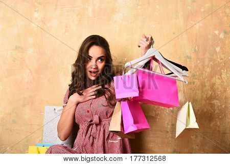 pretty fashionable woman with long brunette curly hair and smiling happy surprised face holds hangers and colorful shopping bags on beige background