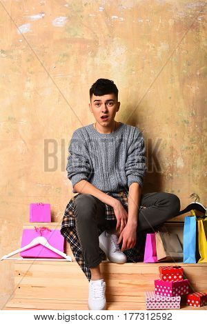 handsome man young caucasian guy in sweater with surprised face near fashionable hangers and colorful shopping bags and gift boxes sitting on wooden stairs on beige background