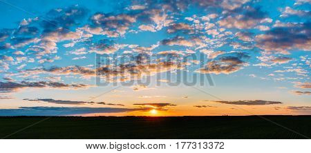 Panorama Of Natural Sunset Sunrise Over Field Or Meadow. Bright Dramatic Sky And Dark Ground. Countryside Landscape Under Scenic Colorful Sky At Sunset Dawn Sunrise. Skyline, Horizon. Warm Colours.