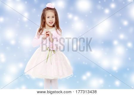 Dressy little girl long blonde hair, beautiful pink dress and a rose in her hair.She folded her arms around his chest.Blue Christmas festive background with white snowflakes.