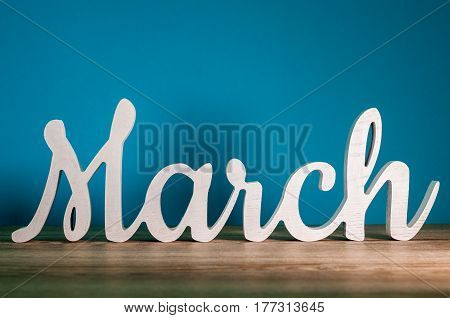 the word MARCH - wooden text at dark blue background. Spring concept.