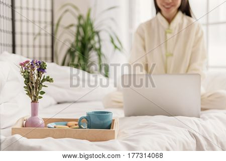 Focus on tray with breakfast for outgoing asian woman laboring notebook computer