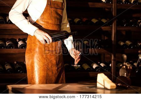Sommelier holding a bottle of wine and glass in his hand. Wine vault location.