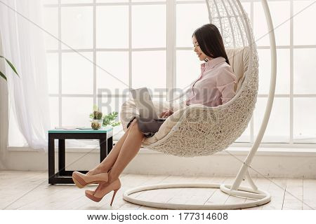 Full length attentive asian woman working on laptop while sitting near wide window on design chair