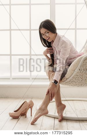 frazzling clever asian female expressing ache in bare feet while sitting on soft chair near shoes