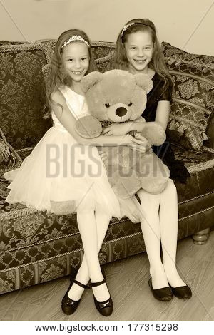 Two adorable little twin girls sitting on sofa hugging a big Teddy bear.Black-and-white photo. Retro style.