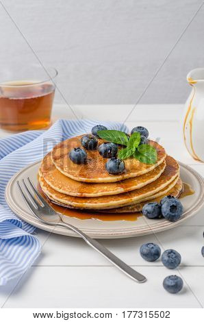 Stack of pancakes with fresh blueberry and caramel syrup.