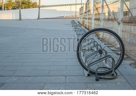 A damaged bike wheel is all that is left of a bicycle chained to a bike stand, a single bicycle wheel on the street due to stealing, Stolen bicycle, Chained bicycle wheel, front wheel locked