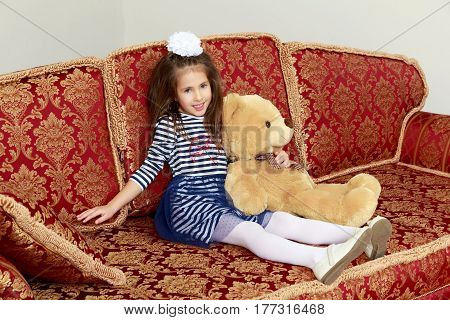 Little girl in blue striped dress and a white bow on her head.Girl sitting on sofa with Teddy bear.