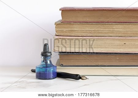 Vintage bottle of ink and pen rests in front of stack of vintage books with room for copy.