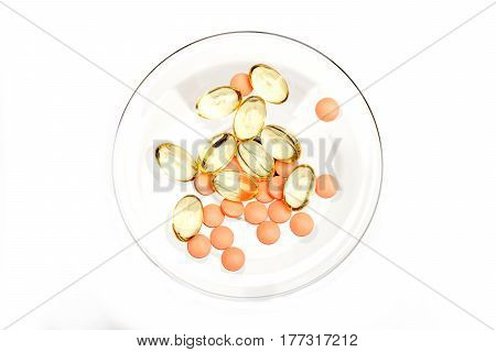 Red Pills And Capsules Of Cod-liver Oil On Glass Stem