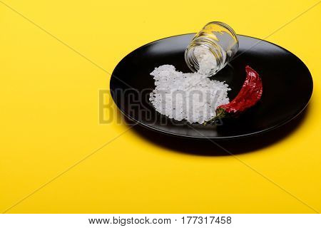 Glass Jar With Salt And Red Pepper On Black Plate
