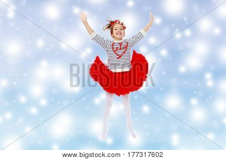 Little girl in a red skirt and bow on her head.She jumps waving her arms.Blue Christmas festive background with white snowflakes.
