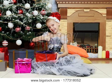 Beautiful little girl in a dress of Princess around the Christmas tree.She sits beside the Christmas tree with a big gift.