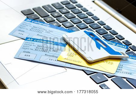 Buying airline tickets online for travel with credit cards and laptop on white table background