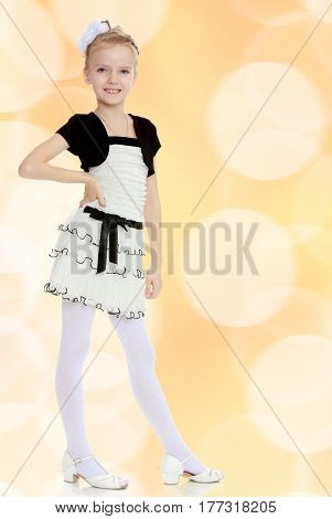 Beautiful little blonde girl dressed in a white short dress with black sleeves and a black belt.The girl is thrusting the leg.