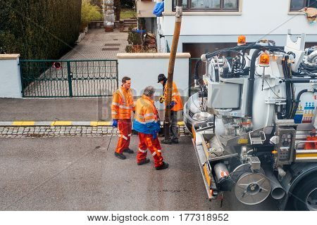 Workers Using Sewerage Truck And Large Pipe Working On The Clogged Street Rain Water