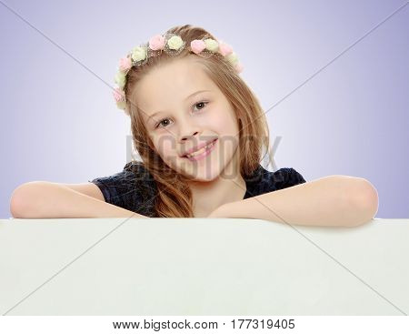 Beautiful little girl with a wreath on his head peeks out from behind the banner.On a light purple gradient background.