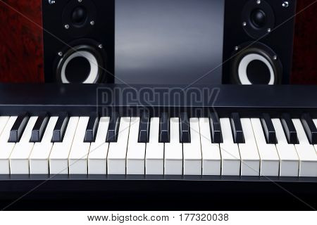 two stereo audio speakers and piano keys closeup on dark background