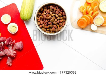healthy dogfood with sliced eggs, fresh vegetables and raw meat on white kitchen table background top view mockup
