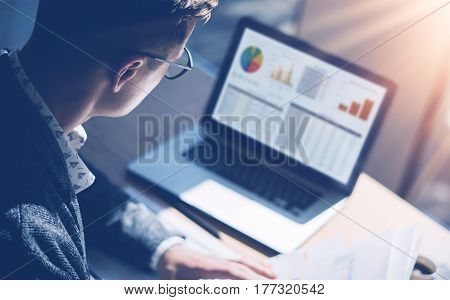 Closeup view of finance market analyst in eyeglasses working at sunny office on laptop while sitting at wooden table.Businessman analyze stock report on notebook screen.Blurred background, horizontal
