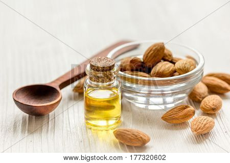 natural cosmetic set with almond oil and bowl of almonds on light wooden table background