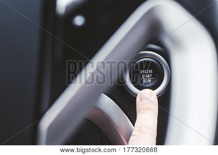 Button for starting the engine and a finger for a person with a shallow depth of field