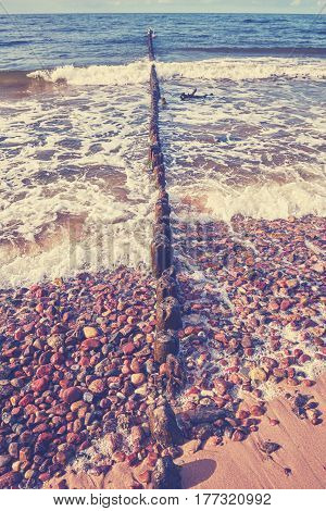 Old Wooden Breakwater On A Beach, Color Toned.