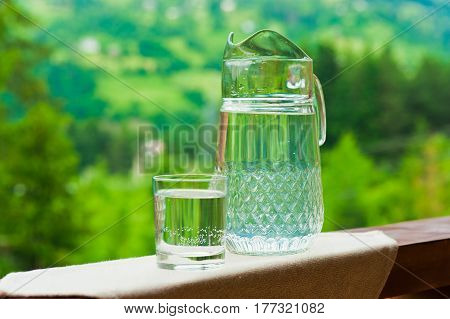 Transparent jug of water on green natural Carpathians background