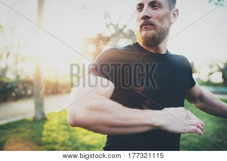 Workout lifestyle concept.Young man stretching his arm muscles before training.Muscular athlete exercising outside in sunny park. Blurred background