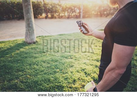 Workout fitness concept.Muscular handsome athlete checking training programm on smartphone application before workout session on city park in the sunny morning.Blurred background